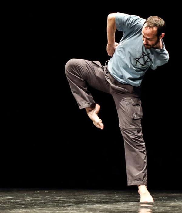 Dance artist Hillel Kogan poses mid performance