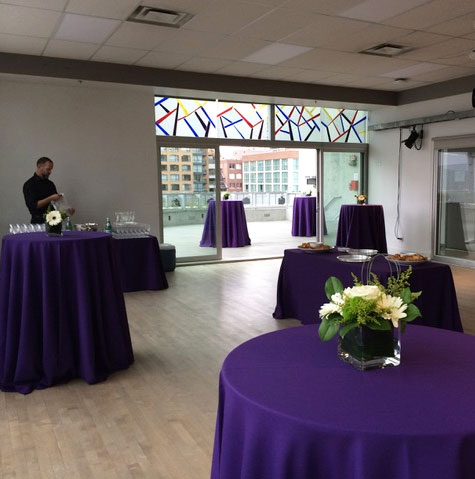 The Marcuse studio at Scotiabank Dance Centre set up for an event with tables covered in tablecloths and flowers on them