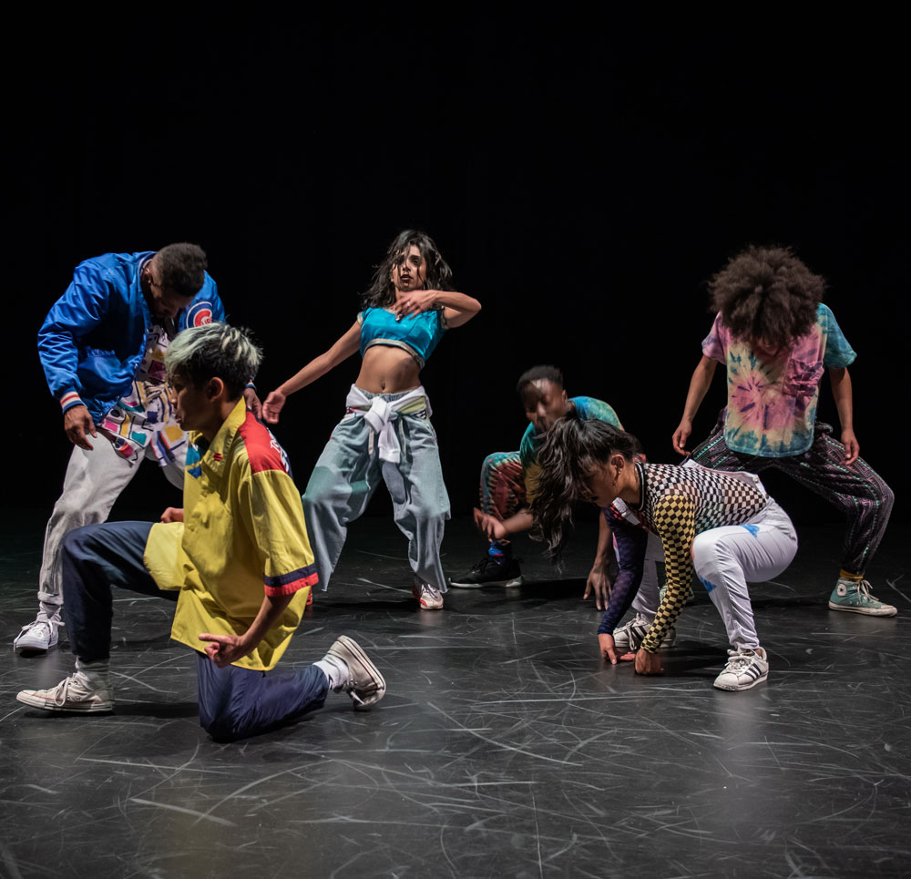Dance artists from Immigrant Lessons pose mid performance