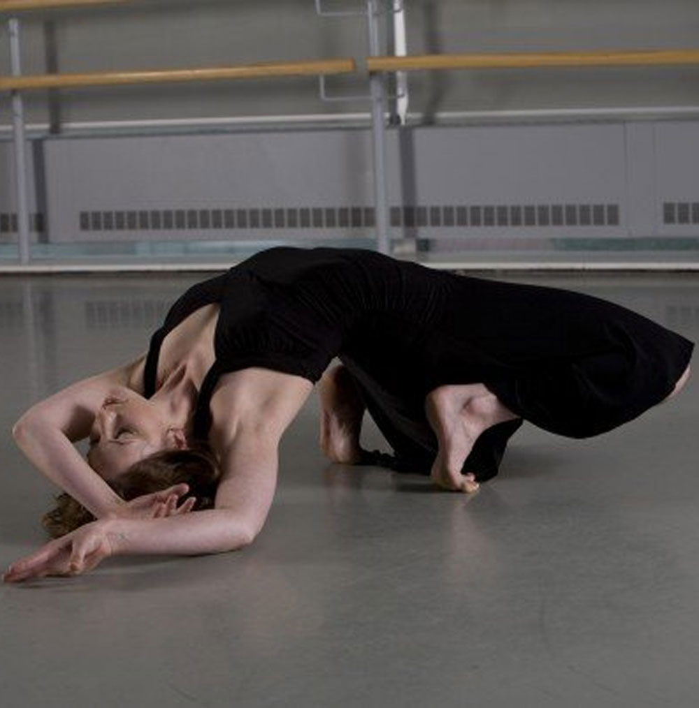 Julia Carr poses on floor during dance performance