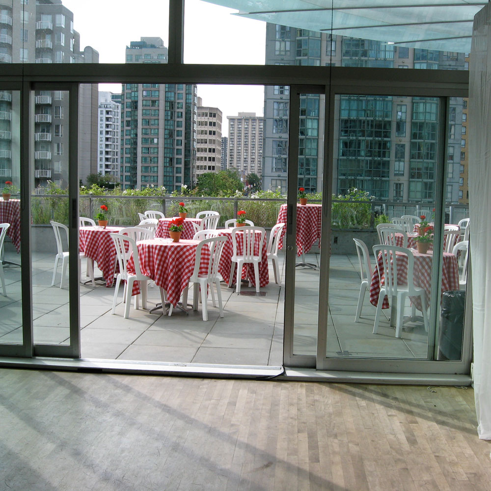 Chairs and tables arranged on the patio of the Scotiabank Dance Centre for a summer event