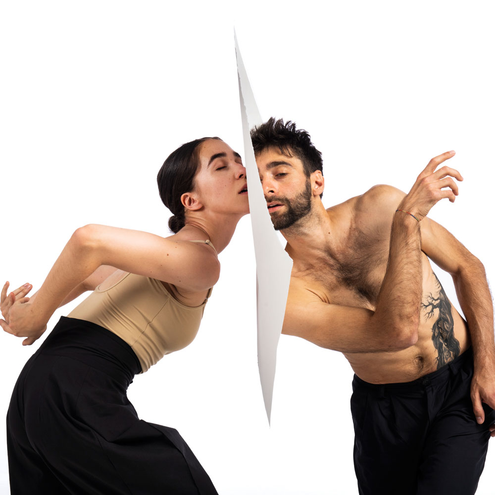 Dance artists from Wen Wei Dance pose with paper between them