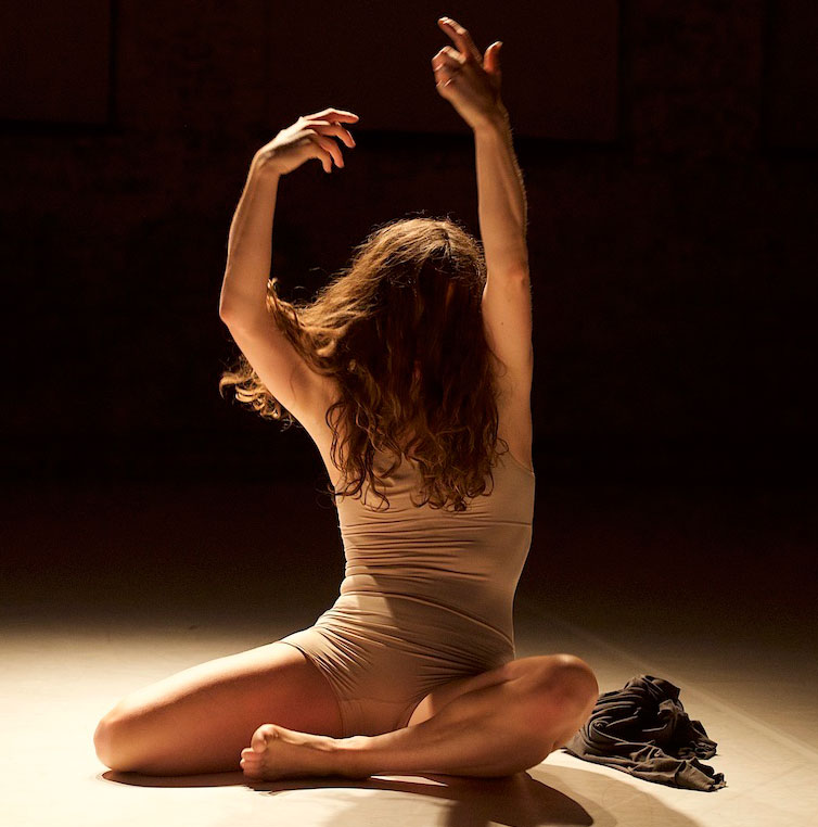 Anouk Froidevaux posing while sitting on the floor in the middle of a dance performance