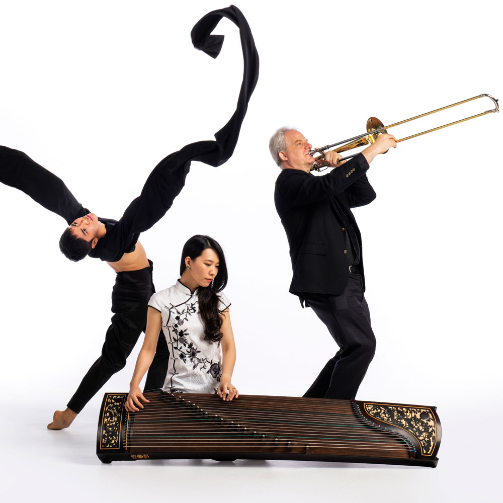Dancer from Wen Wei Dance posing with two musicians from Turning Point Ensemble