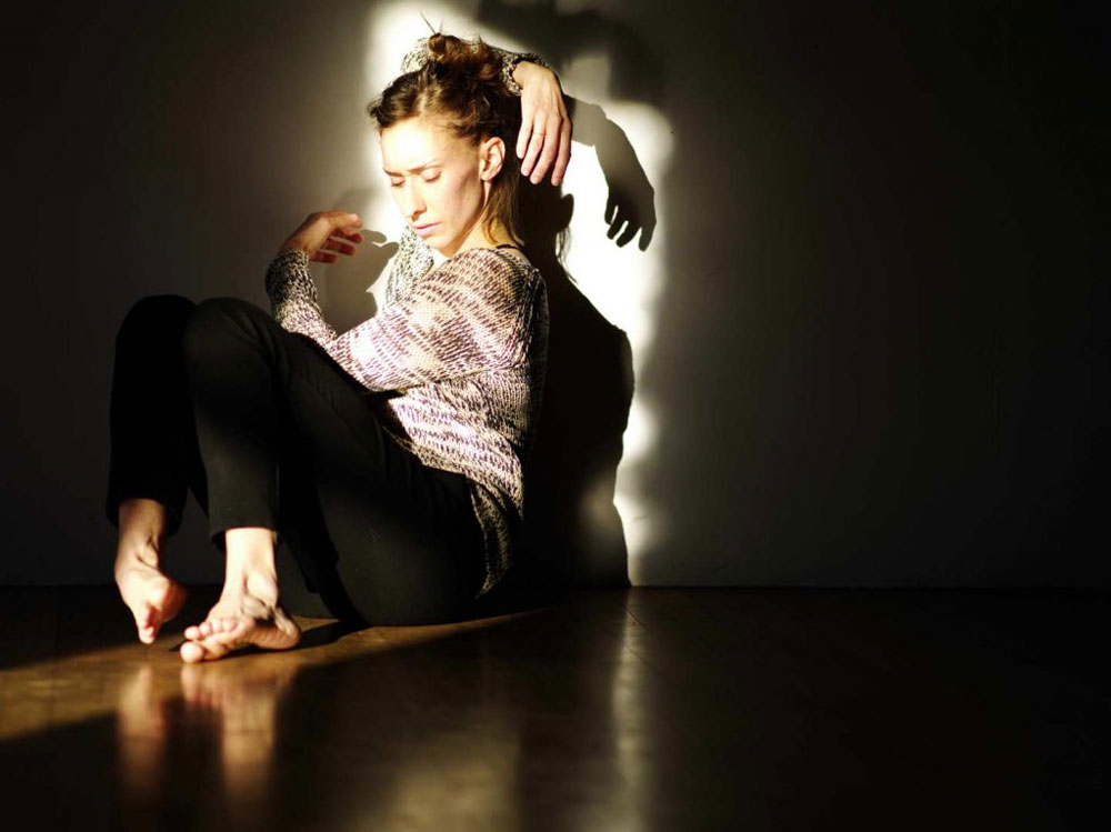Olivia Shaffer sits on the floor with arms wrapped around her mid performance