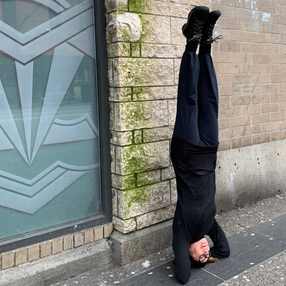 Dance artist P. Megan Andrews stands on her head outside a building
