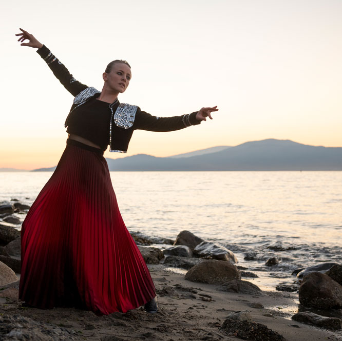 Dance artist Maria Avila poses on a beach while wearing a flamenco costume