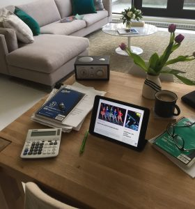 A work at home set up with a tablet, coffee and a calculator on a desk