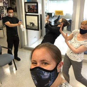 Dance Centre staff pose with masks and cleaning spray