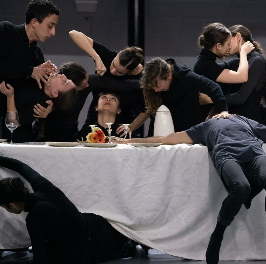 Dance artists crowded around a table, performing in Pigulim
