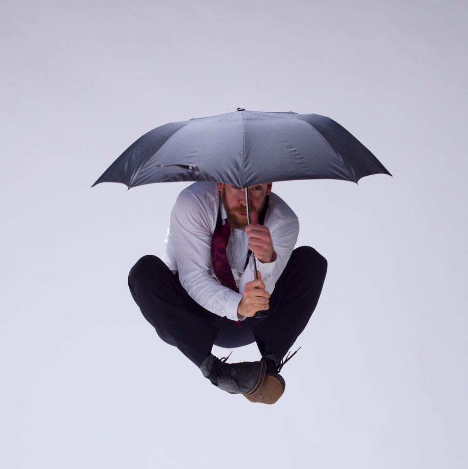 Dance artist Shay Kuebler jumps in the air while holding an umbrella
