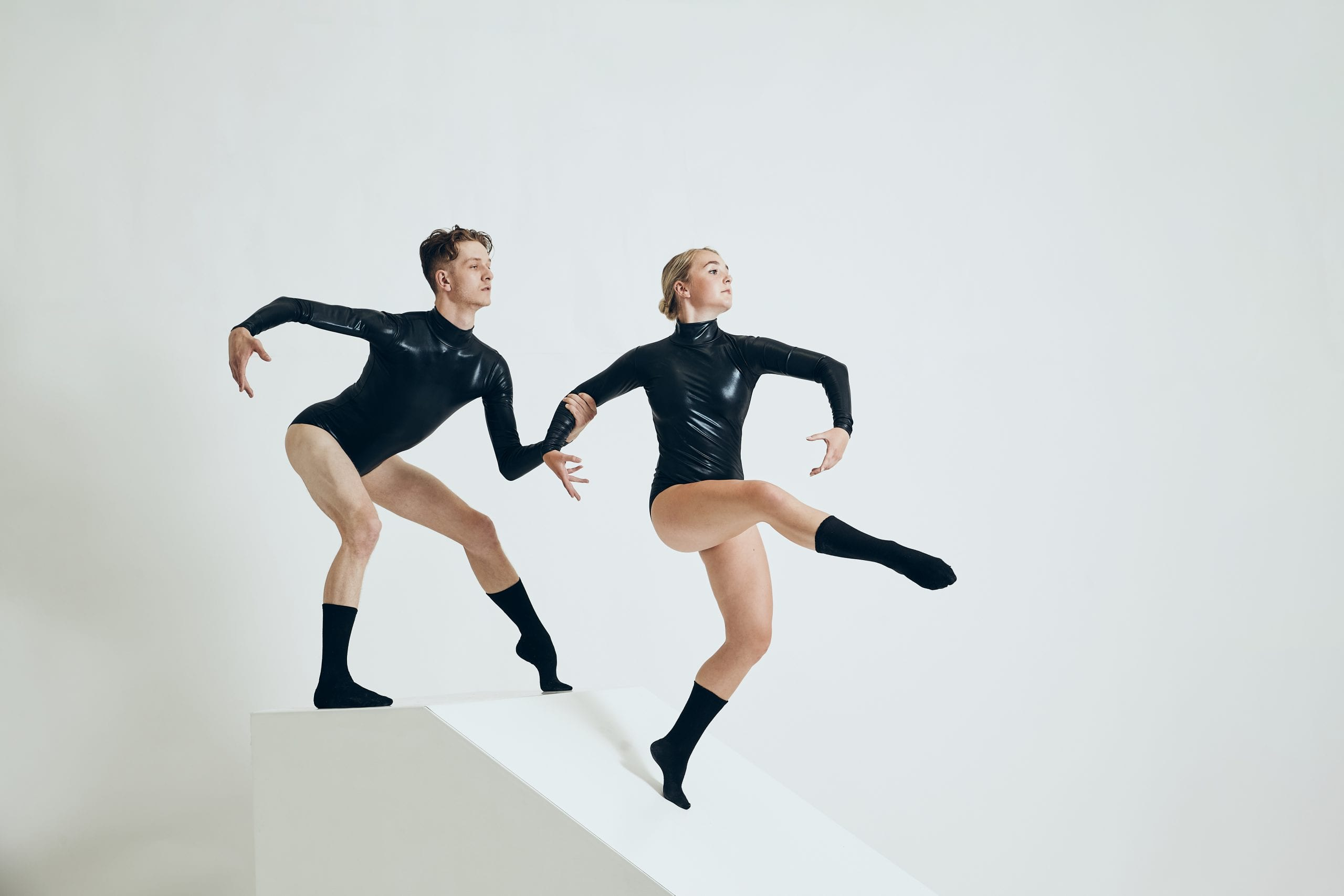 Two dance artists pose while wearing black songs and shiny black leotards