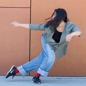 Dance artist Shana Wolfe poses mid side lunge with arms out