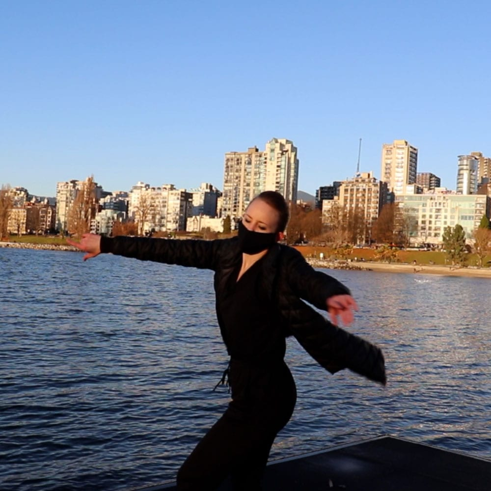 Dance artist Maria Avila performs on a dock in the Vancouver Harbour while wearing a mask
