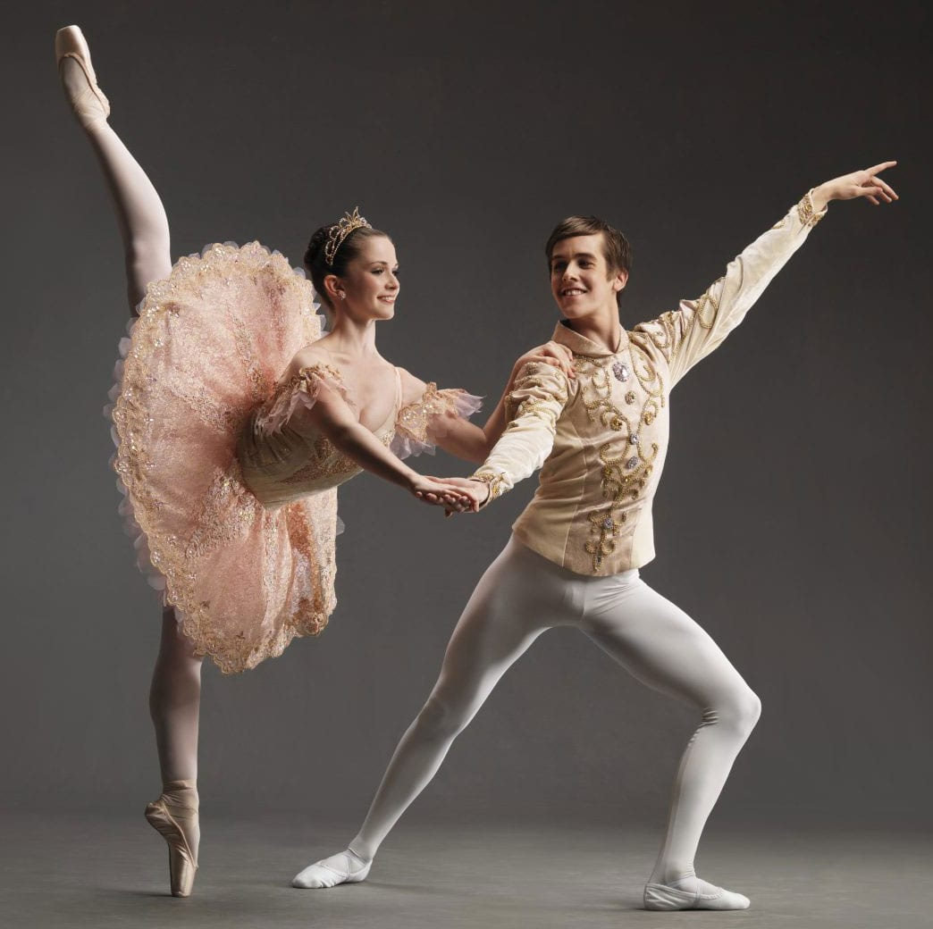 Two ballet dancers pose in full ballet costumes