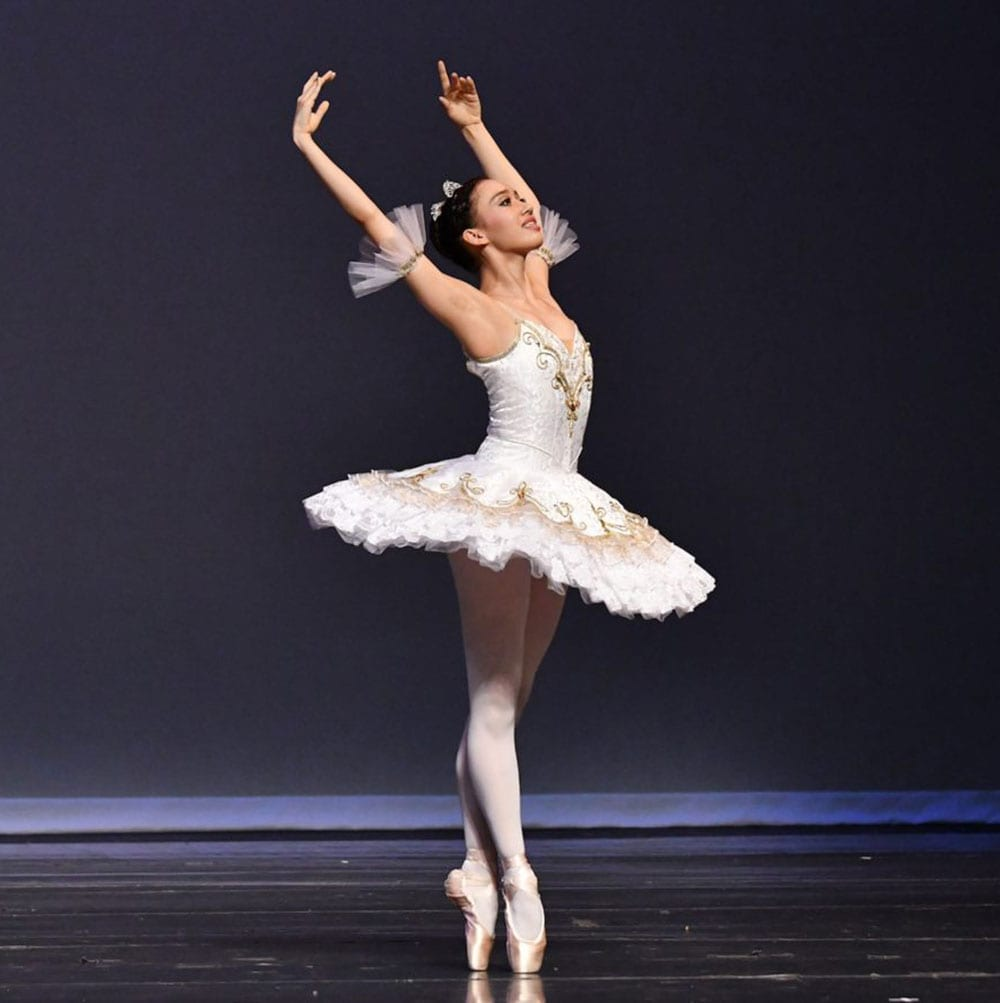 Ballerina stands on pointe wearing a full tutu