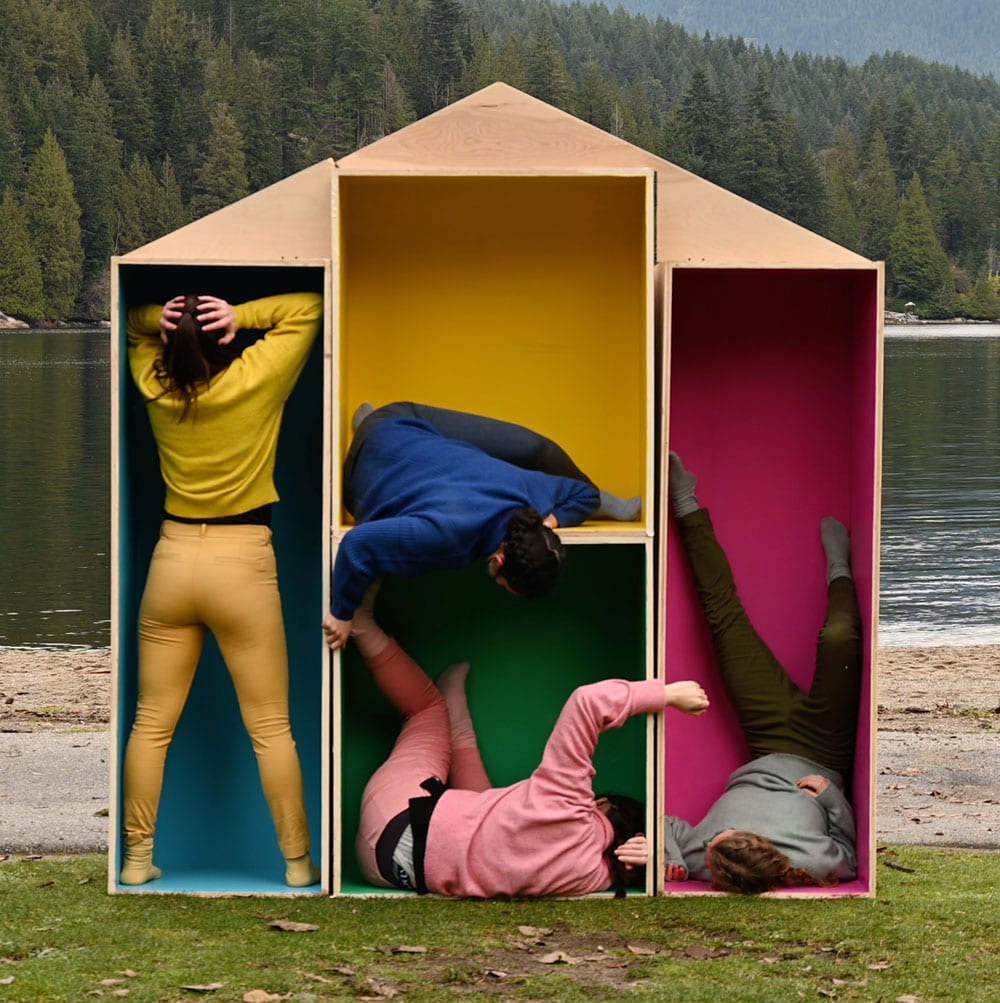 Dance artists pose inside makeshift shelves shaped in a house on a river bank