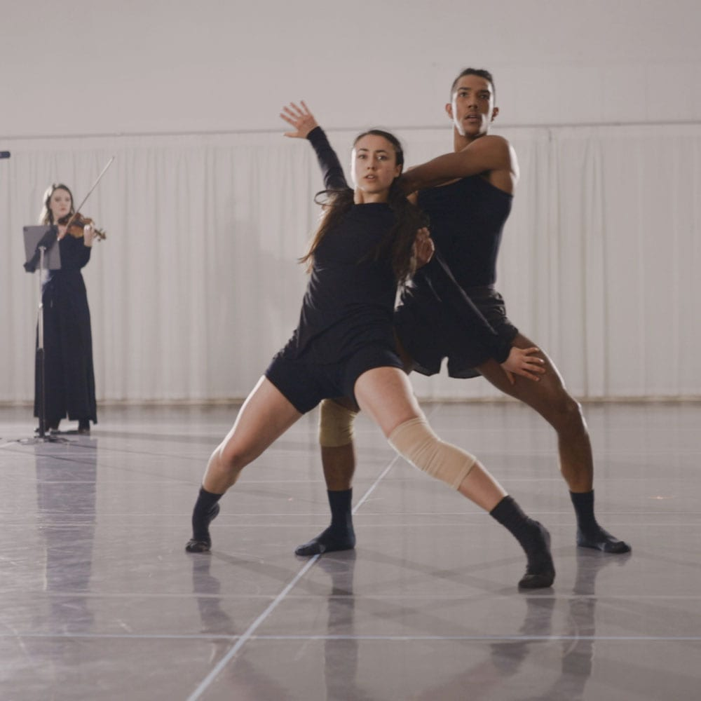 Dance artist Xin Hui Ong posing mid rehearsal with partner while violinist plays behind them