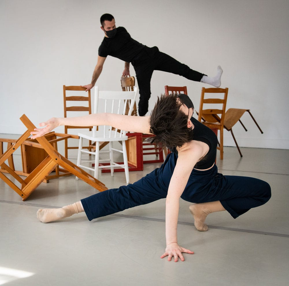 Dance artists perform over chairs and other furniture