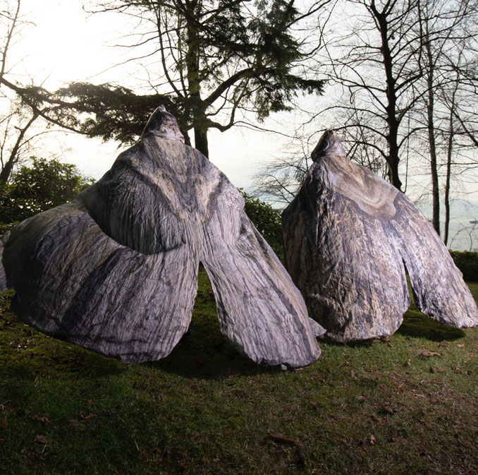 Two dance artists stand in a field wearing large moth costumes covering their entire backs