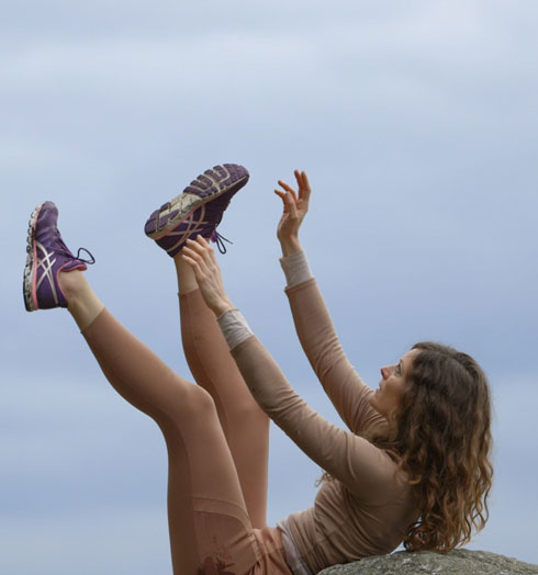 Dance artist Anouk Froidevaux leans on a rock with her legs and arms extended into the air