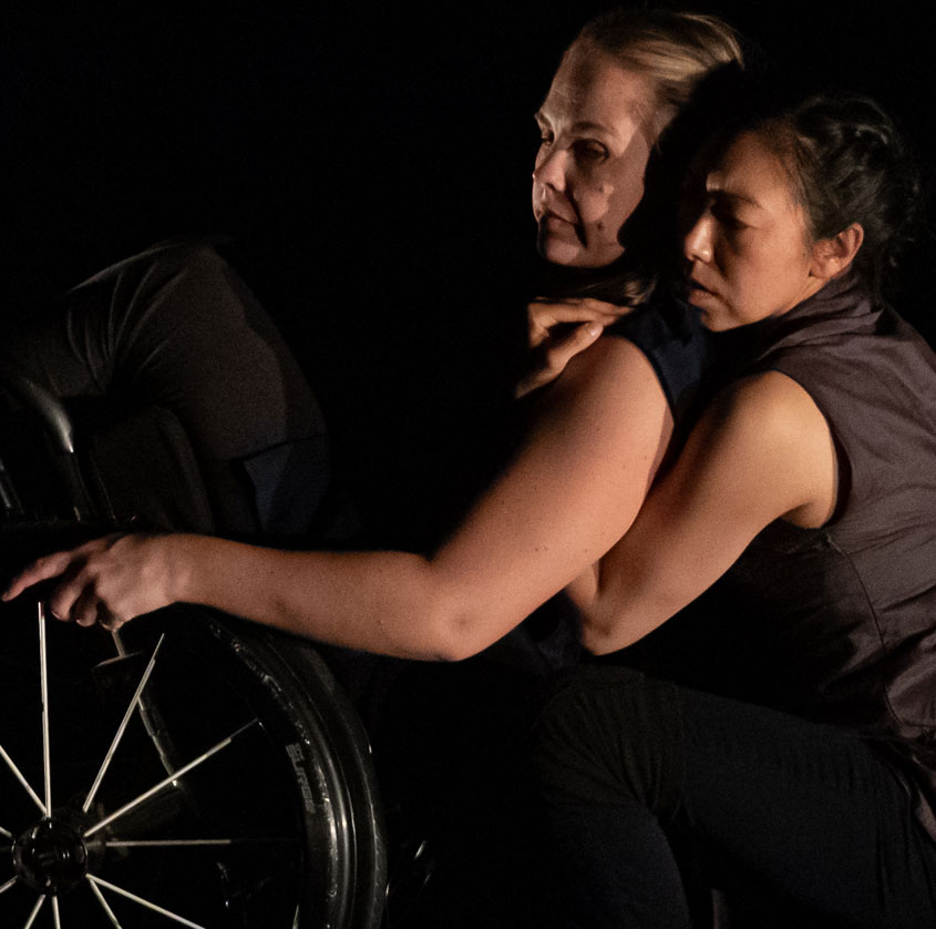 A dance artist in a wheelchair leans back and is held by another dance artist mid performance