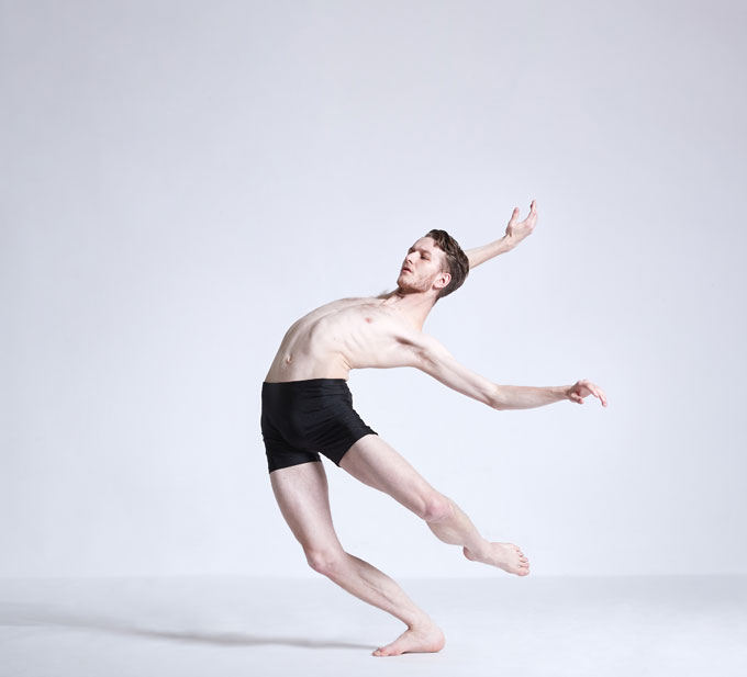 Male dance artist leans backwards with arms and one leg extended