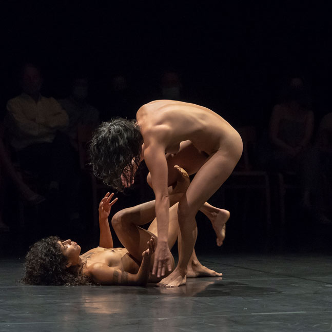 Female dance artists perform on stage while nude.