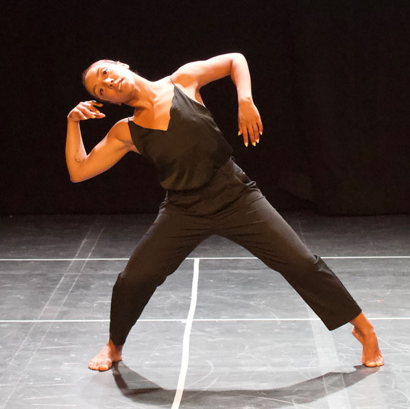 A female dance artist wearing a black jumpsuit poses with arms bent, leaning of her right leg
