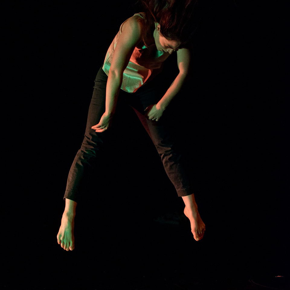A female dance artist mid jump with her head bent over