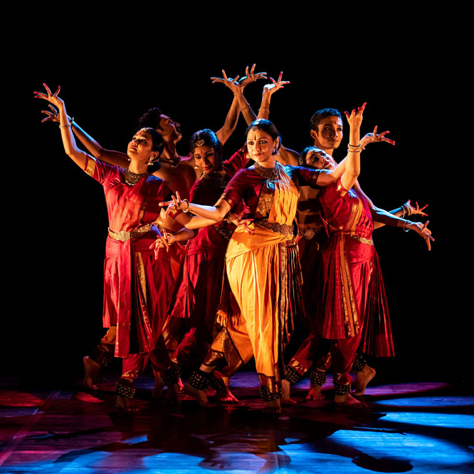 Rama Vaidyanathan and ensemble dancers pose together with their arms extended and bent on a stage